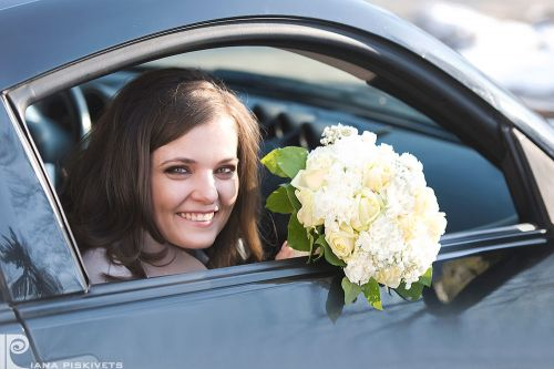 Newlyweds in a car, a beautiful woman with flowers, wedding car, bride's bouquet, a photo shoot in Warsaw, a white wedding dress of marriage, photo shoot. Professional wedding photographer Poland registrar in Pruszkow bride with a bouquet.