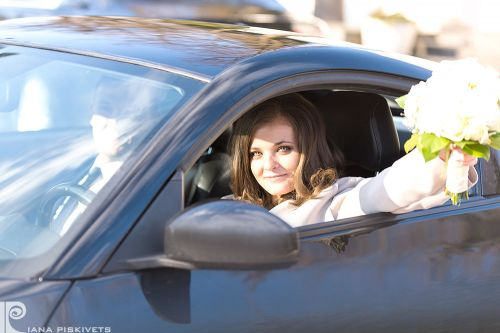 Newlyweds in a car, a beautiful woman with flowers, wedding car, bride's bouquet, a photo shoot in Warsaw, a white wedding dress, romantic photo shoot. Professional wedding photographer in Poland registrar in Pruszkow bride with a bouquet.