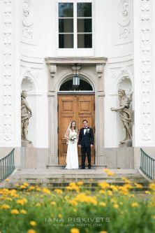 Щаслива красива наречена у шлюбній сукні фаті з букетом білих квітів центрі Варшави на чорному автомобілі мерседесі з білими трояндами фотозйомка весільного торжества професійний фотограф Варшава Польща фотокнига вінчання красиві фотографії краса кохання